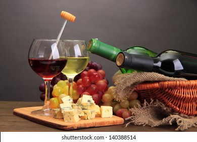 Composition with wine, blue cheese and grape on wooden table, on grey background