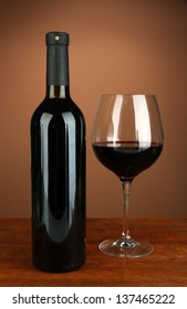 Composition of wine bottle and  glass of red wine, on color background