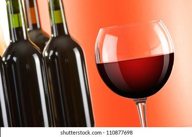 Composition with wineglass and bottles of red wine