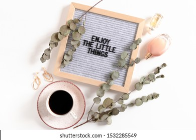 Composition with women's accessories, mug of coffee, eucalyptus branches and letterboard with quote Enjoy the little things