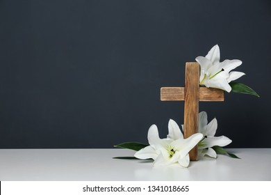 Composition with wooden cross and blossom lilies on table against color background, space for text