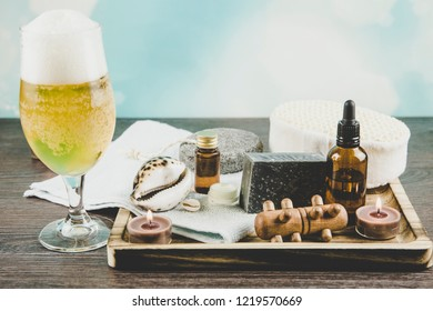 Composition wooden tray with group of different spa essentials, beard oil, gray clay soap, natural sponge, candles burning, aroma oil glass of beer on light blue bokeh background. Spa for men concept.