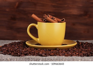 Composition of the yellow cup with coffee beans and cinnamon on wooden background