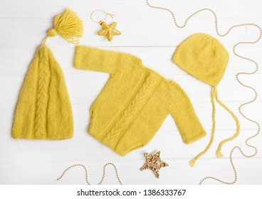 Composition of yellow knitted suit and hats with decorations