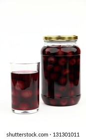 Compote with cherries in jar and glass
