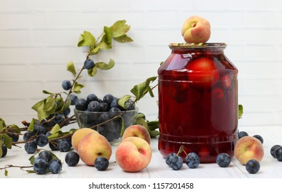 Compote with peaches and berries of blackthorn in jar on a white background. Harvest for the winter.