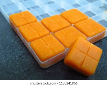 Compounded, orange square troches (lozenges) in a white, plastic mold on a countertop in a compounding pharmacy.