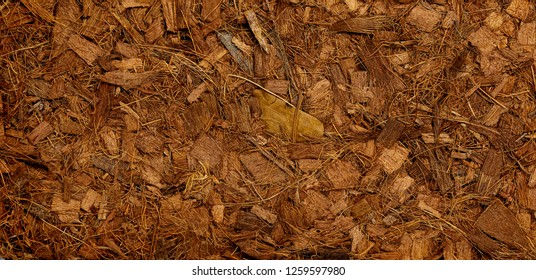 Compressed bale of ground coconut shell fibers (coir), surface background.
