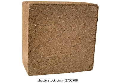 A compressed bale of ground coconut shell fibers (coir), a renewable resource (peat moss alternative). Isolated. 12MP camera.