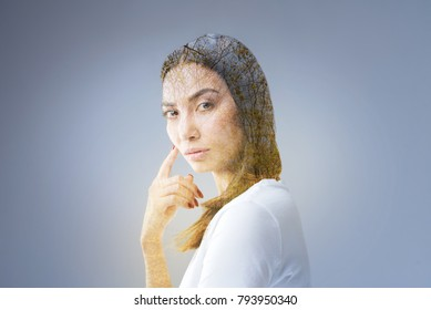 Compromising thought. Musing reflective serious woman standing on the grey background while touching her face with finger and gazing  at the camera