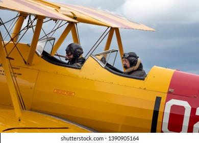 Compton Abbas, Dorset/United Kingdom - 09/08/2018: Pilot and co-pilot of an American Boeing Stearman biplane prepare to leave Compton Abbas airfield near Shaftesbury in Dorset
