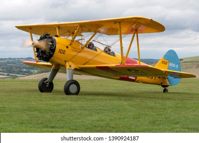 Compton Abbas, Dorset/United Kingdom - 09/08/2018: The smiling crew of Boeing spearman biplane prepare to take off from Compton Abbas airfield near Shaftesbury in Dorset
