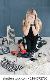 compulsive buyer and consumerism concept. shopaholic regretting purchasing too much clothing stuff on the store sale. girl covering her face with hands surrounded by clothes shoes and bags.