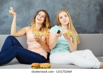 Compulsive overeating, food addiction, mindless snacking, fast-food, delight, enjoyment, treat, appetite, hunger. Two cute young women sitting at coach with tv remote eating burgers and chips greedily