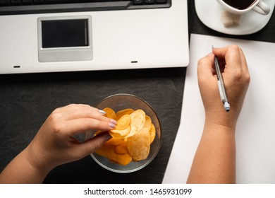Compulsive overeating, mindless snacking, junk food, unhealthy meals. Woman eating chips from bowl at her workplace