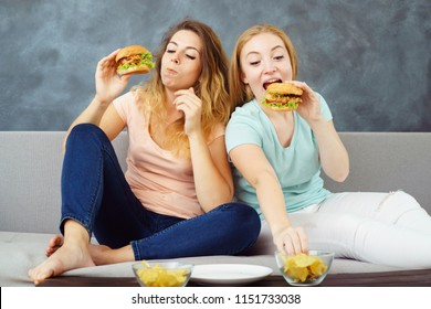 compulsive overeating, mindless snacking, sedentary lifestyle, hunger, pleasure, enjoyment. Two young women sitting on coach greedily devouring burgers and chips