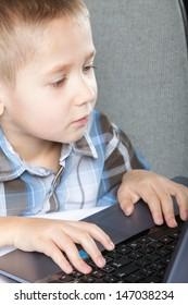Computer addiction child boy with laptop notebook black background