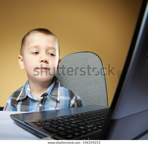 Computer addiction child boy with laptop notebook brown background