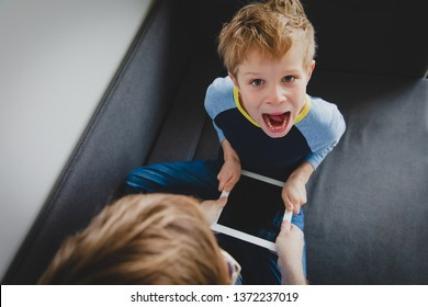 computer addiction - father taking touch pad from angry child