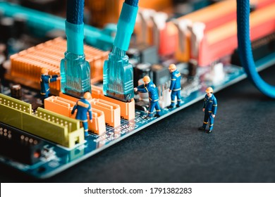 Computer assembly - technicians connecting sata cable on motherboard