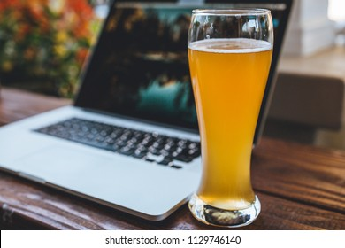 Computer and beer on a wooden desk or table. modern workflow while outdoors. working on tech.