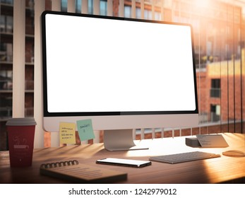 Computer with blank screen with keyboard on desk in office building interior