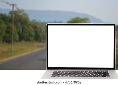 computer with blank screen on blur image of tree in forest