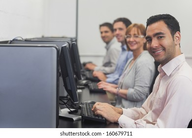 Computer class sitting in front of computers smiling at camera