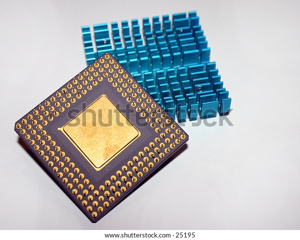 computer CPU from the downside with pins and core displayed. in the background a passive CPU heatsink