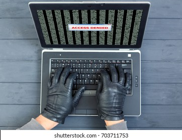 Computer Criminal using brute force password break on Laptop staying on vintage natural wood background