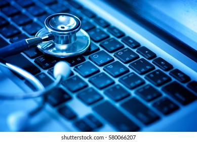 Computer or data analysis - Stethoscope over a laptop computer keyboard toned in blue