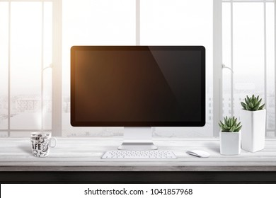 Computer display with blank screen for mockup in office or work room. Window and sun light in background. Cup of coffee and two plants beside.