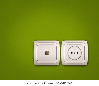 Computer and electrical outlets on green wall background