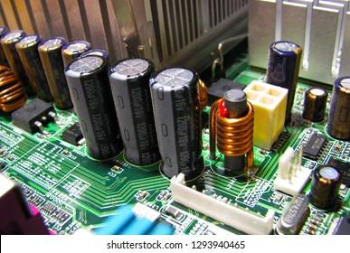 Computer electronic printed circuit board with capacitors, resistors, and ICs. Macro closeup photo of a green motherboard PCB.