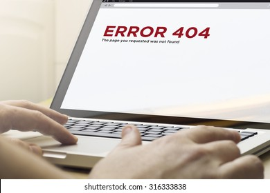 computer error concept: man using a laptop with error 404 on the screen. Screen graphics are made up.