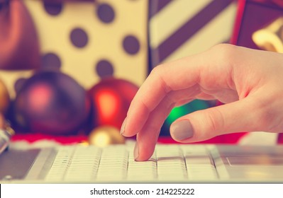 Computer, female hand and christmas gifts at background