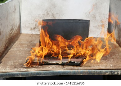 Computer Fire. A laptop computer engulfed in flames of hot fire. Smoke and Fire burn and melt a computer.  Computer damage or data destruction concepts. Room for text.