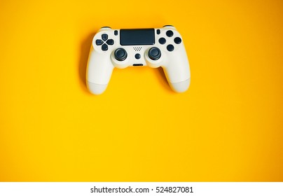 Computer game competition. Gaming concept. White joystick on yellow background.