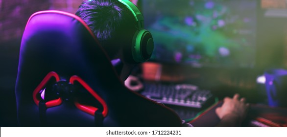 computer games, playing place, young gamer plays computer games with headphones,
