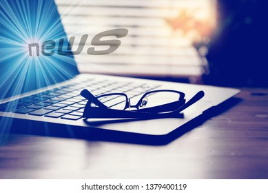 A computer, glasses and the news