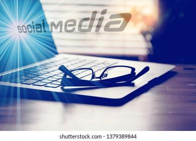 A computer, glasses and social media