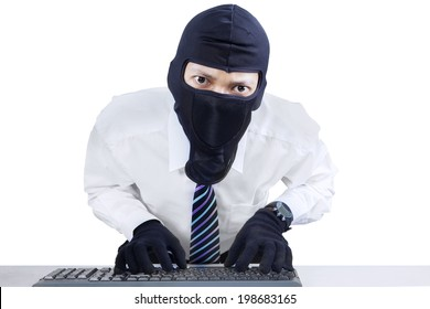 Computer hacker - businessman wearing mask stealing data from computer.
