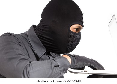 Computer hacker - businessman wearing mask stealing data from computer. Isolated white background