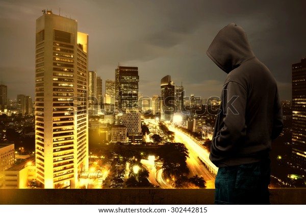 Computer hacker silhouette of hooded man standing on the top of the building at night