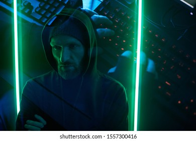 Computer hacker standing and remembering the password from computer system in dark room with green lights