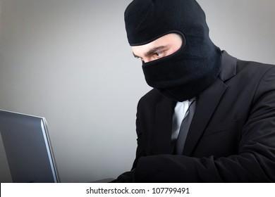 Computer hacker in suit and tie over grey background