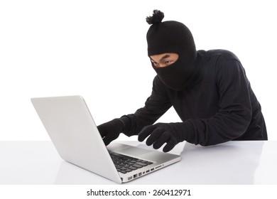 Computer hacker wearing mask stealing data on laptop computer