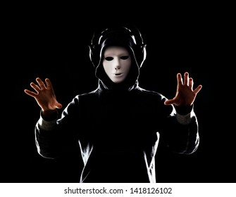 Computer hacker in white mask and hoodie. Obscured dark face. Data thief, internet fraud, darknet and cyber security concept.