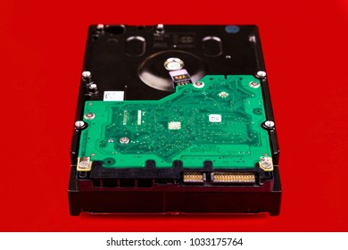 Computer hard drive, front view, on a red background. Data storage