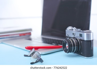 Computer keyboard, cactus and camera lie on table